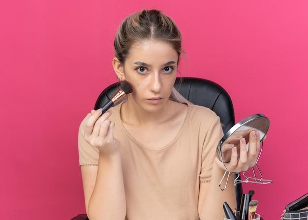 Młoda piękna dziewczyna siedzi przy stole z narzędziami do makijażu, stosując róż w proszku, trzymając lustro izolowane na różowej ścianie
