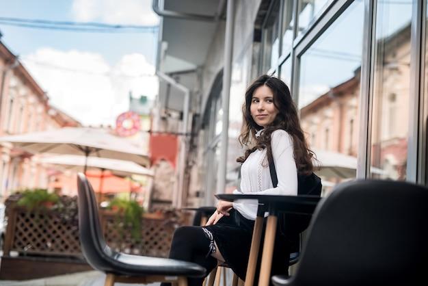 Młoda piękna dziewczyna siedzi w kawiarni i czeka na jej cappuccino, czas letni