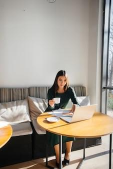 Młoda piękna dziewczyna siedzi w kawiarni, pracuje przy komputerze i komunikuje się w sieciach społecznościowych.