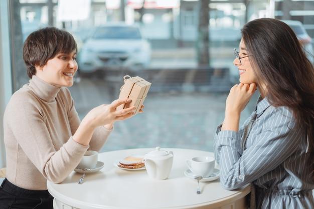 Młoda piękna dziewczyna siedzi w kawiarni ze swoją przyjaciółką i odbiera prezent