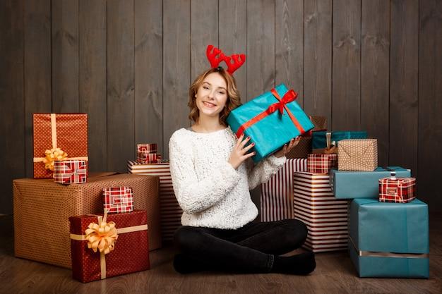 Młoda piękna dziewczyna siedzi wśród świątecznych prezentów nad drewnianą ścianą