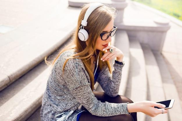 Młoda piękna dziewczyna słuchania muzyki na ulicy.