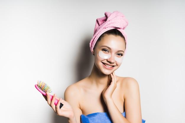 Młoda piękna dziewczyna śmieje się, trzyma w rękach grzebień, po kąpieli, z ręcznikiem na głowie