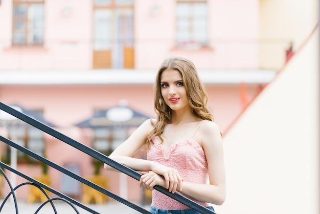 Młoda piękna dziewczyna spaceruje po mieście. piękny model spacerujący po mieście. patrząc na historyczną część miasta. pojęcie turystyki i wolności.