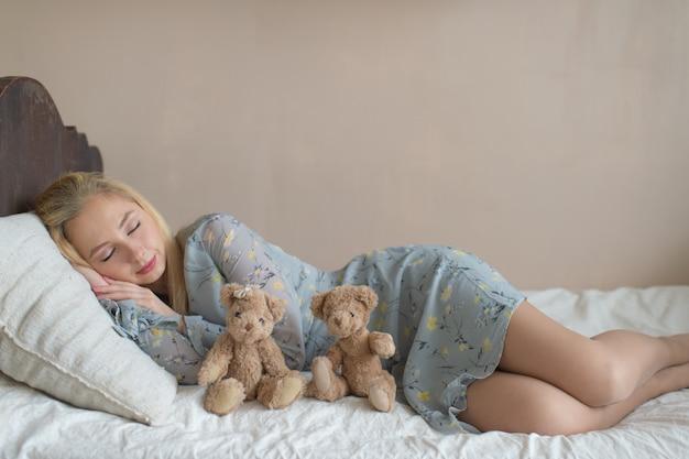 Młoda piękna dziewczyna śpi na łóżku z zabawkami dziecko jak dziecko.