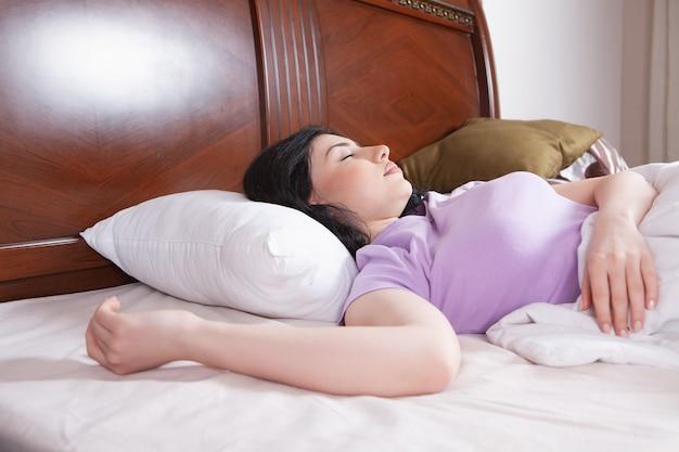 Młoda piękna dziewczyna śpi w łóżku