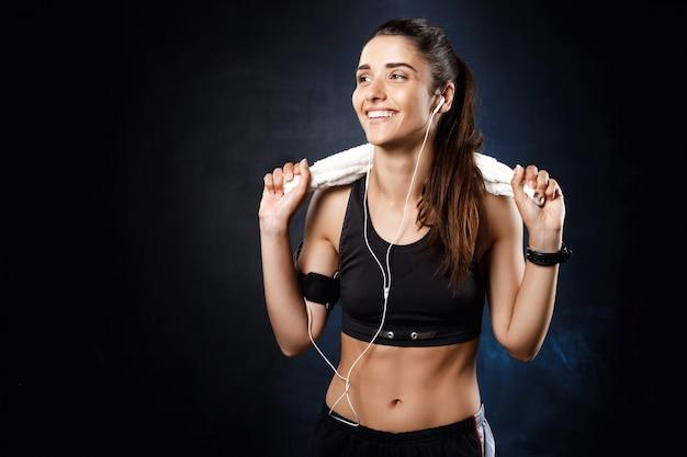 Młoda piękna dziewczyna sportive słuchania muzyki na ciemnej ścianie.