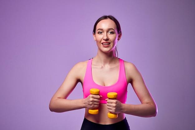 Młoda piękna dziewczyna sportowa w legginsy i top robi ćwiczenia z hantlami. zdrowy tryb życia.