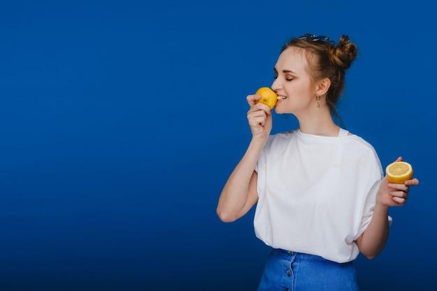 Młoda piękna dziewczyna stojąca na niebieskim tle trzyma w ręku cytryny i gryzie.