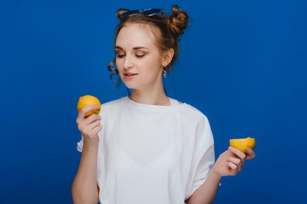Młoda piękna dziewczyna stojąca na niebieskim tle trzymając cytryny w ręku i gryząc