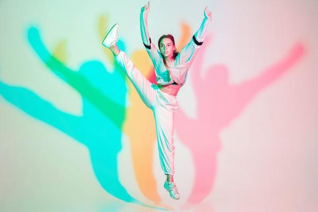 Młoda piękna dziewczyna tańczy hip-hop, styl ulicy na białym tle na studio