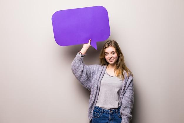 Młoda piękna dziewczyna trzyma fioletowy bańka tekstu, na białym tle