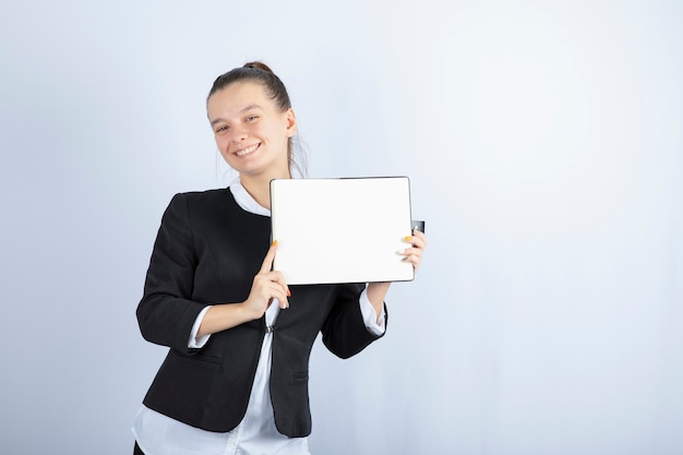 Młoda piękna dziewczyna trzyma książkę, uśmiechając się na białym tle. wysokiej jakości zdjęcie