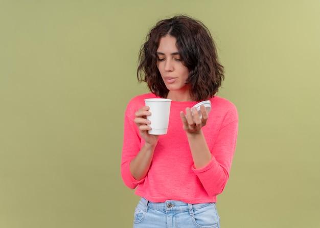 Młoda piękna dziewczyna trzyma plastikową filiżankę kawy i dmuchanie na nią na odosobnionym zielonym tle z miejsca na kopię