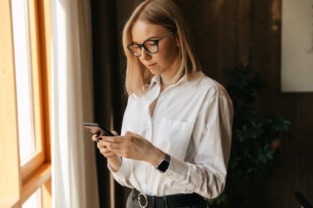 Młoda piękna dziewczyna trzyma w dłoniach smartfon, pisze na czacie i odpowiada na wiadomości rozmówcy.