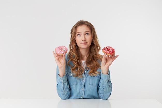 Młoda piękna dziewczyna trzyma w rękach pączki, jest na diecie, ale marzy o jedzeniu pączków, wyobraża sobie, jakie są smaczne i słodkie na białym tle.