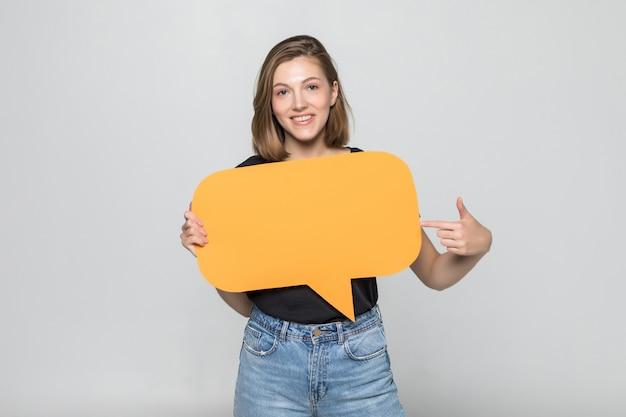 Młoda piękna dziewczyna trzyma zieloną bańkę tekstu, odizolowane