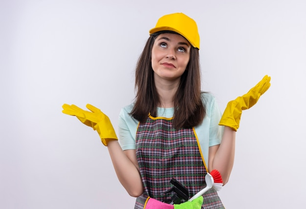 Młoda piękna dziewczyna ubrana w fartuch, czapkę i gumowe rękawiczki, patrząc zdezorientowany, rozkładając ręce na boki
