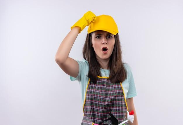 Młoda piękna dziewczyna ubrana w fartuch, czapkę i rękawice gumowe podnosząc pięść, krzycząc z gniewną twarzą