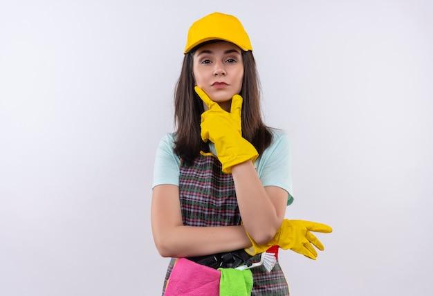 Młoda piękna dziewczyna ubrana w fartuch, czapkę i rękawiczki gumowe, patrząc na kamery ręką na brodzie, patrząc pewnie