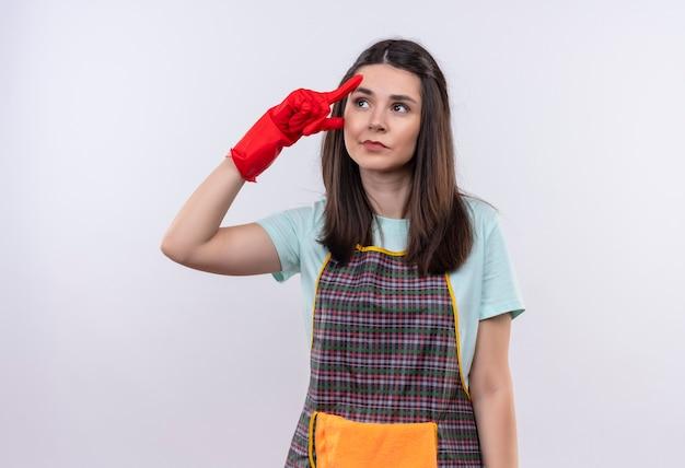 Młoda piękna dziewczyna ubrana w fartuch i gumowe rękawiczki patrząc w górę, wskazując jej świątynię, próbując zapamiętać ważną rzecz