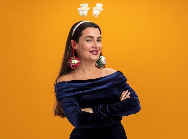Młoda piękna dziewczyna ubrana w niebieską sukienkę i świąteczną obręcz do włosów, trzymającą bombki na uszach - odizolowana na pomarańczowej ścianie