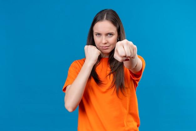 Młoda piękna dziewczyna ubrana w pomarańczową koszulkę pozuje jak bokser pokazując pięść do kamery, patrząc pewnie stojąc na odosobnionym niebieskim tle
