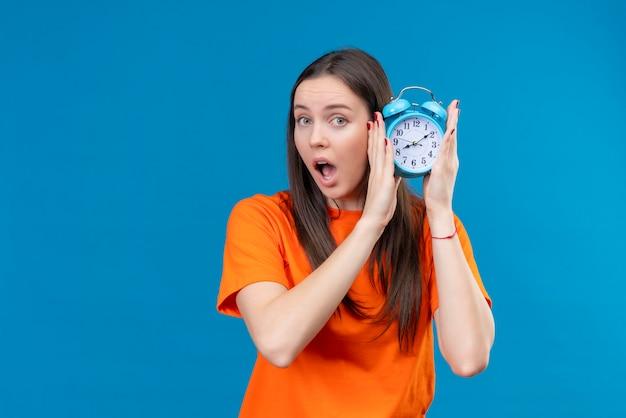 Młoda piękna dziewczyna ubrana w pomarańczowy t-shirt trzyma budzik patrząc zdziwiony i zaskoczony stojąc na na białym tle niebieskim tle