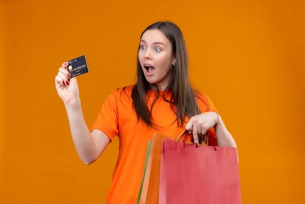 Młoda piękna dziewczyna ubrana w pomarańczowy t-shirt trzymając pakiet papieru i kartę kredytową uśmiechnięty radośnie zaskoczony i wyszedł stojąc na białym tle pomarańczowy