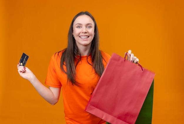 Młoda piękna dziewczyna ubrana w pomarańczowy t-shirt trzymając pakiet papieru i kartę kredytową uśmiechnięty wesoło stojąc na białym tle pomarańczowy