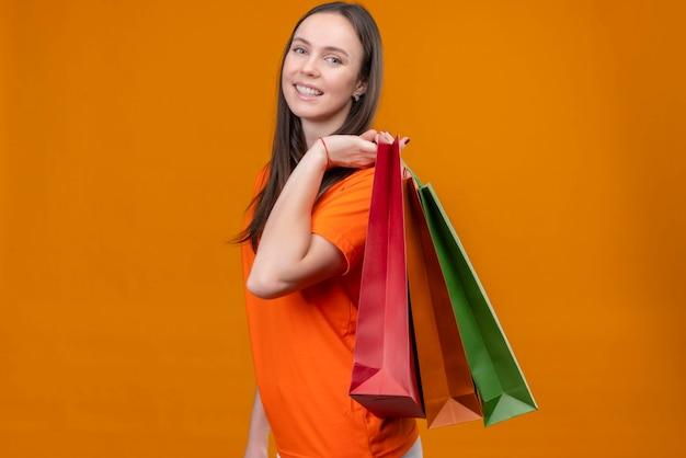 Młoda piękna dziewczyna ubrana w pomarańczowy t-shirt trzymając papierowe torby patrząc na kamery uśmiechnięty wesoło stojąc na na białym tle pomarańczowym tle