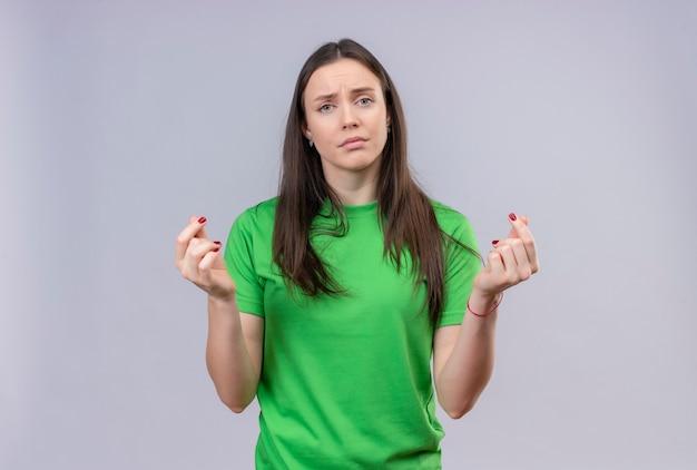 Młoda piękna dziewczyna ubrana w zieloną koszulkę patrząc na kamery niezadowolona, pocierając palce robiąc gest gotówki, prosząc o pieniądze stojąc na białym tle