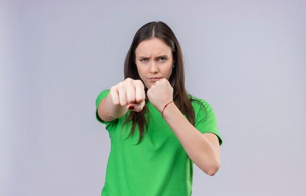 Młoda piękna dziewczyna ubrana w zieloną koszulkę pozująca jak bokser zaciskający pięść do kamery, patrząc z marszczoną twarzą stojącą na białym tle