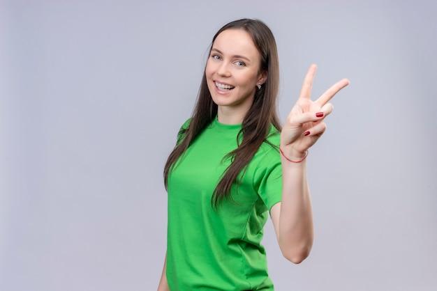Młoda piękna dziewczyna ubrana w zieloną koszulkę, uśmiechnięta wesoło, pokazująca i skierowana w górę palcami numer dwa lub znak zwycięstwa stojący na białym tle
