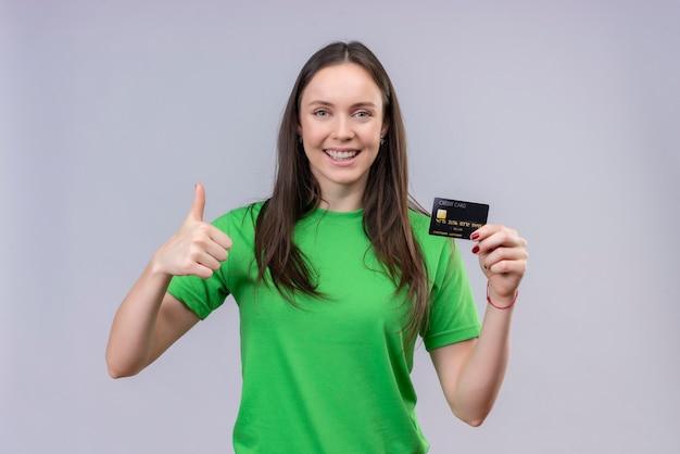 Młoda piękna dziewczyna ubrana w zieloną koszulkę wyszła i szczęśliwa trzymając kartę kredytową, pokazując kciuki do góry, uśmiechając się wesoło stojąc na białym tle