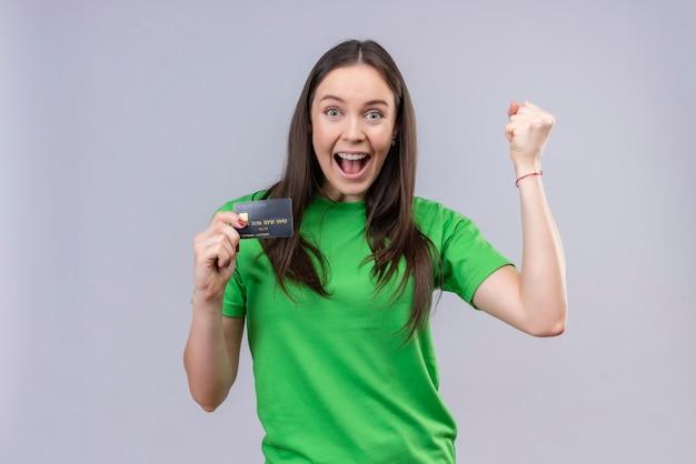 Młoda piękna dziewczyna ubrana w zieloną koszulkę wyszła i szczęśliwa trzymając kartę kredytową, uśmiechając się radośnie podnosząc pięść, ciesząc się z jej sukcesu stojąc na białym tle
