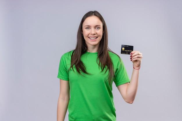 Młoda piękna dziewczyna ubrana w zielony t-shirt pozytywny i szczęśliwy trzyma kartę kredytową uśmiechnięty wesoło stojąc na białym tle