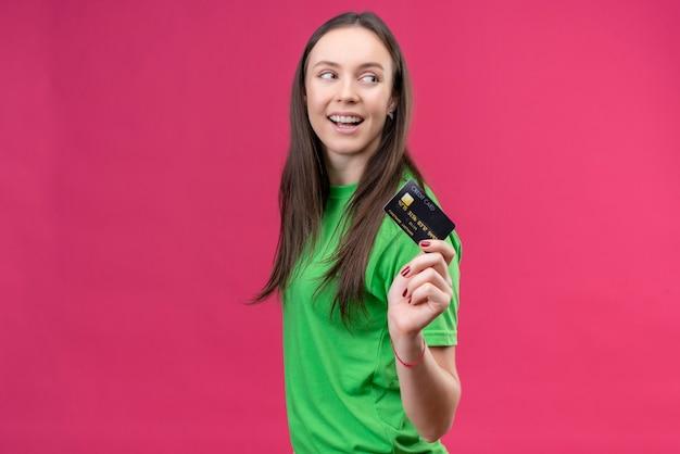 Młoda piękna dziewczyna ubrana w zielony t-shirt trzyma kartę kredytową patrząc na bok uśmiechnięty radośnie szczęśliwy i pozytywny pozycja na białym tle różowym tle