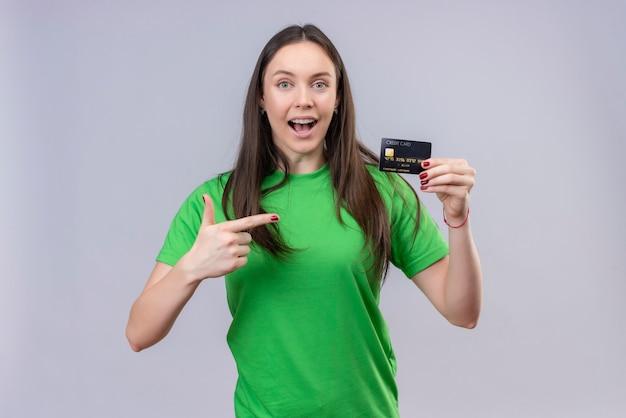 Młoda piękna dziewczyna ubrana w zielony t-shirt wyszedł i szczęśliwy trzyma kartę kredytową, wskazując palcem na to stojąc na białym tle