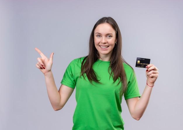 Młoda piękna dziewczyna ubrana w zielony t-shirt wyszedł i szczęśliwy trzymając kartę kredytową, wskazując palcem na bok stojącej na białym tle