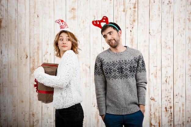Młoda piękna dziewczyna ukrywa świąteczny prezent od swojego chłopaka.
