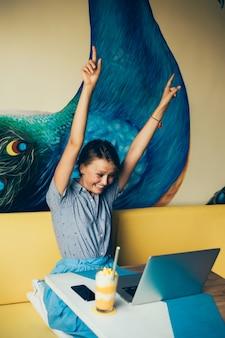 Młoda piękna dziewczyna używa laptopa w kawiarni, surfując w internecie