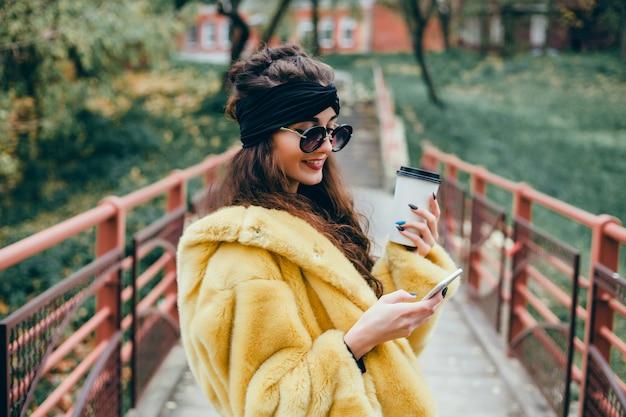 Młoda piękna dziewczyna używa smartfona na ulicy, surfowania w internecie i picia kawy