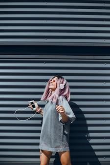 Młoda piękna dziewczyna używa smartfona na ulicy, surfując po internecie i słuchając muzyki