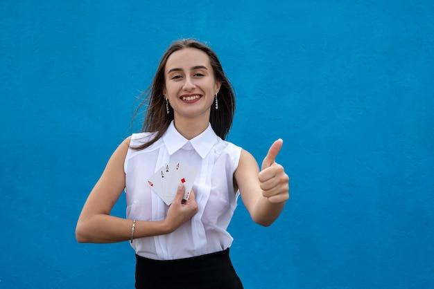 Młoda piękna dziewczyna w białej bluzce trzyma karty do gry w pokera na niebieskiej ścianie
