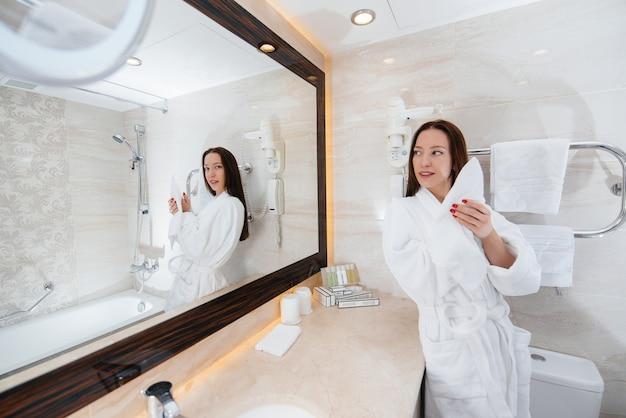 Młoda piękna dziewczyna w białej pięknej łazience. świeży dzień dobry w hotelu.