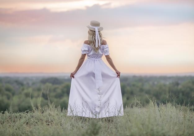 Młoda piękna dziewczyna w białej sukni i kapeluszu patrzy na zachód słońca.