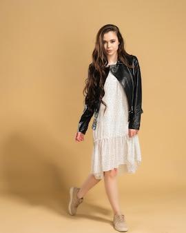 Młoda piękna dziewczyna w białej sukni w groszki i czarnej skórzanej kurtce pozuje na pastelowej pomarańczy.