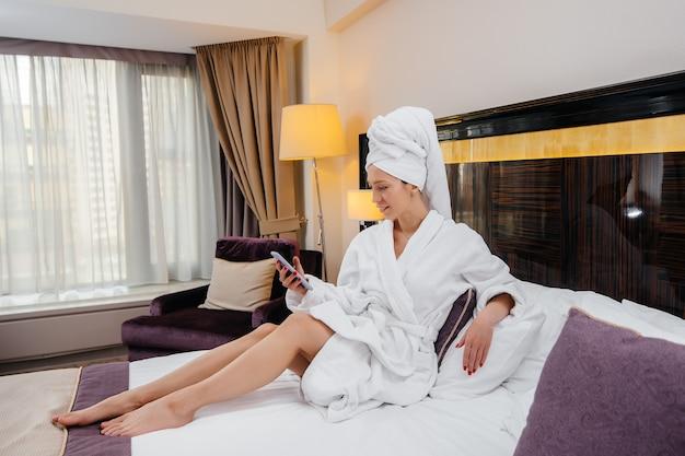Młoda piękna dziewczyna w białym płaszczu robi sobie selfie telefonem w swoim pokoju hotelowym.