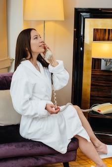 Młoda piękna dziewczyna w białym płaszczu rozmawia przez telefon w swoim pokoju hotelowym.
